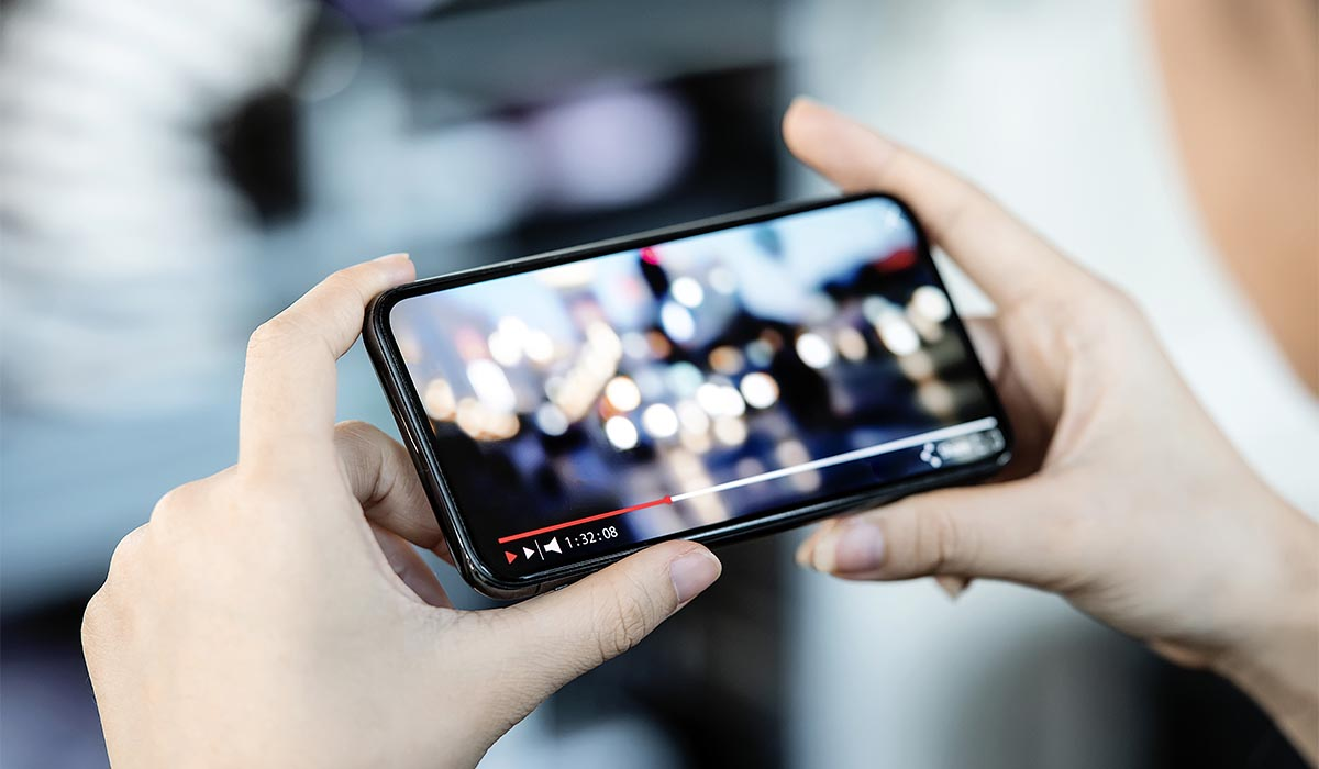 man kijkt videomarketing op smartphone